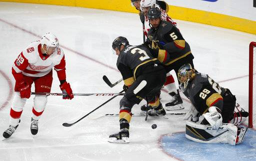 Vegas Golden Knights goalie Marc-Andre Fleury blocks a shot by Detroit Red Wings right wing Anthony Mantha, left, during the third period of an NHL hockey game Friday, Oct. 13, 2017, in Las Vegas. (AP Photo/John Locher)