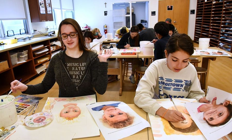 Fiona Conneely, left, and Sarah McDermott work on their Memory Project portraits in art class at St. Viator.