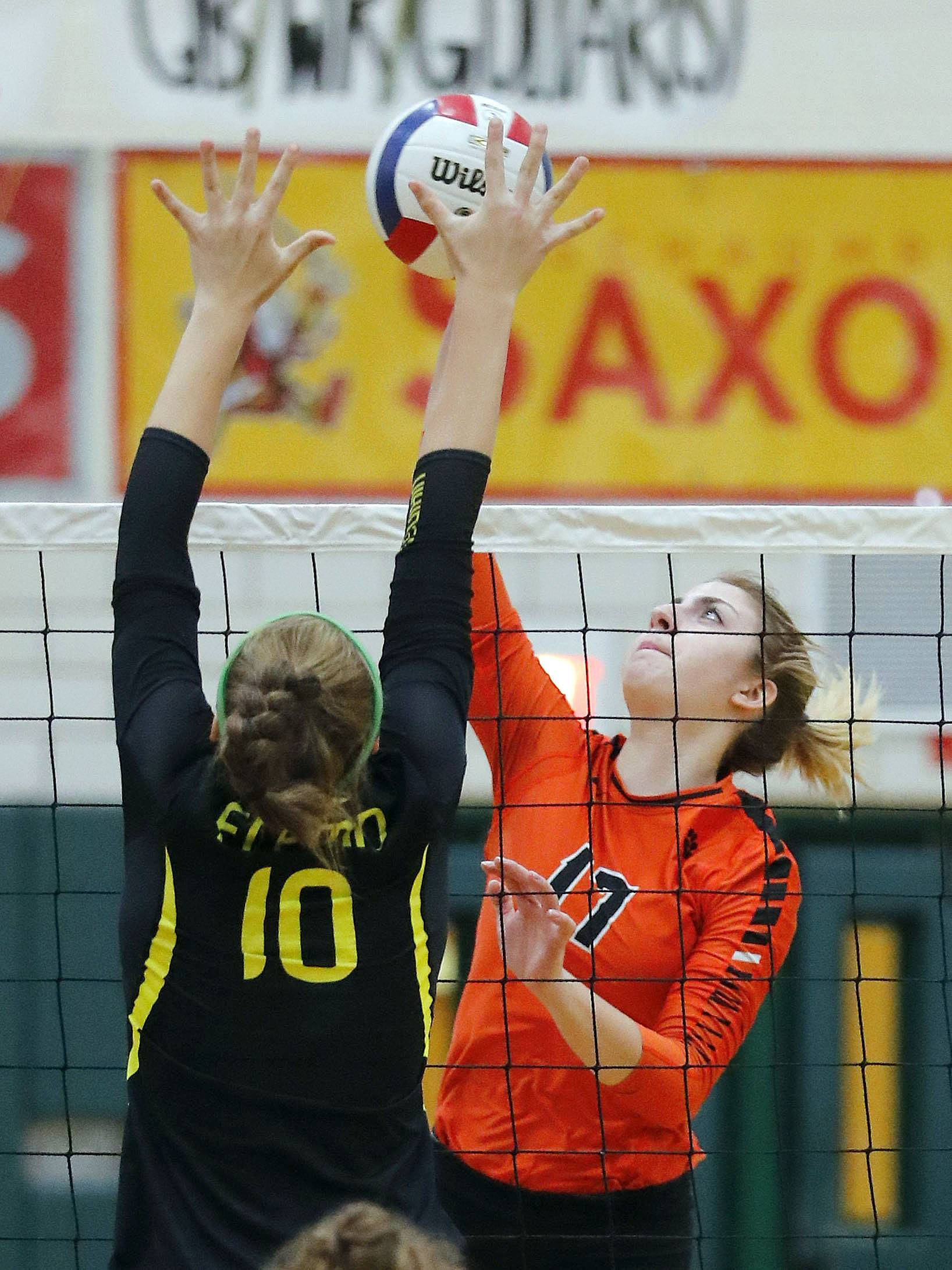 Libertyville's Anna Valente, right, spikes one at Fremd's Peyton Hooker on Monday at Fremd.