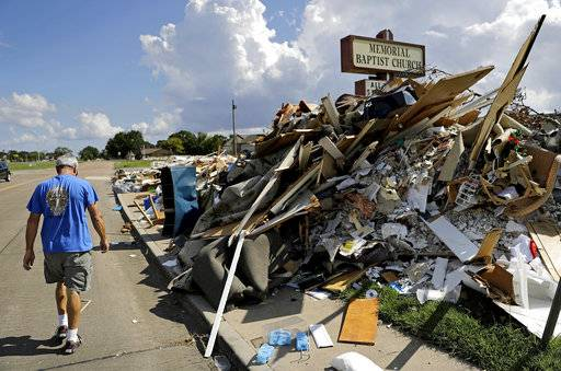 "Wayne Christopher walks by a pile of debris outside the church he'd attended his whole life damaged from Hurricane Harvey in Port Arthur, Texas, Monday, Sept. 25, 2017. He and his wife had come here every Sunday and every Wednesday for more than four decades. This church is where he was baptized, where he met his high school sweetheart, then married her 46 years ago. ""We have a lot of memories here. This is my home. I've been here all my life,"" said Christopher. (AP Photo/David Goldman)"
