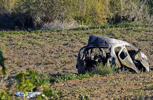 The wreckage of the car of investigative journalist Daphne Caruana Galizia lies next to a road in the town of Mosta, Malta, Monday, Oct. 16, 2017. Malta's prime minister says a car bomb has killed an investigative journalist on the island nation. Prime Minister Joseph Muscat said the bomb that killed reporter Daphne Caruana Galizia exploded Monday afternoon as she left her home in a town outside Malta's capital, Valetta. (AP Photo/Rene Rossignaud)