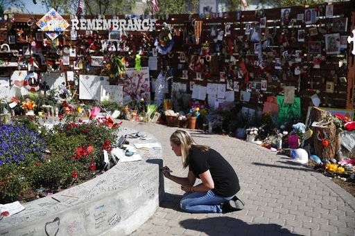 Jenni Tillett writes a message at the Las Vegas Community Healing Garden, Monday, Oct. 16, 2017, in Las Vegas. The garden was built as a memorial for the victims of the recent mass shooting in Las Vegas. (AP Photo/John Locher)