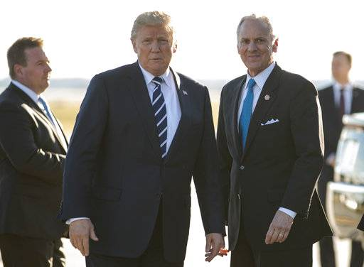 President Donald Trump stands on the tarmac with South Carolina Gov. Henry McMaster as he arrives on Air Force One at Greenville Spartanburg International Airport, in Greer, S.C., Monday, Oct. 16, 2017, en route Greenville, S.C., for a fundraiser for McMaster. (AP Photo/Carolyn Kaster)