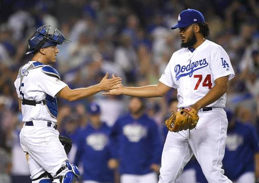 Los Angeles Dodgers relief pitcher Kenley Jansen, right, celebrates the team's 5-2 win with catcher Austin Barnes after Game 1 of baseball's National League Championship Series against the Chicago Cubs in Los Angeles, Saturday, Oct. 14, 2017.(AP Photo/Mark J. Terrill)