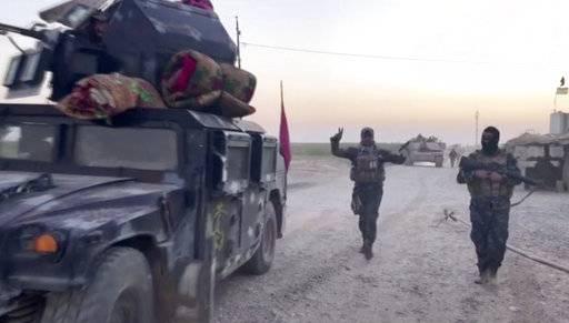 This image made from a video shows Iraqi soldiers and military vehicles in the Qatash area towards Kirkuk gas plant, south of Kirkuk, Iraq, Monday, Oct. 16, 2017. Iraqi state media say federal troops have entered disputed territories occupied by the nation's Kurds. The move comes three years after Kurdish militias seized the areas outside their autonomous region to defend against an advance by the Islamic State extremist group. (APTN via AP)