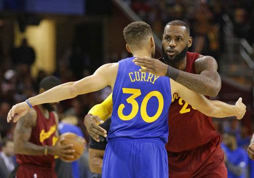 FILE - This Sunday, Dec. 25, 2016, file photo shows Cleveland Cavaliers' LeBron James, right, hugging Golden State Warriors' Stephen Curry before an NBA basketball game, in Cleveland. The Warriors and Cavaliers are being penciled in to meet in the NBA Finals once again. They're going to drive most of the conversation this season, a fact that is not lost on the league or its TV partners. When the season tips off Tuesday, Cleveland will take the center stage first, followed by the Warriors.(AP Photo/Tony Dejak, File)