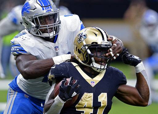 Detroit Lions linebacker Jarrad Davis (40) commits a facemansk penalty as New Orleans Saints running back Alvin Kamara (41) carries in the second half of an NFL football game in New Orleans, Sunday, Oct. 15, 2017. The Saints won 52-38. (AP Photo/Bill Feig)