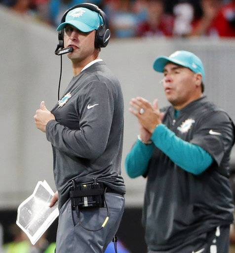 Miami Dolphins head coach Adam Gase, left, watches play against the Atlanta Falcons during the first half of an NFL football game, Sunday, Oct. 15, 2017, in Atlanta. (AP Photo/David Goldman)
