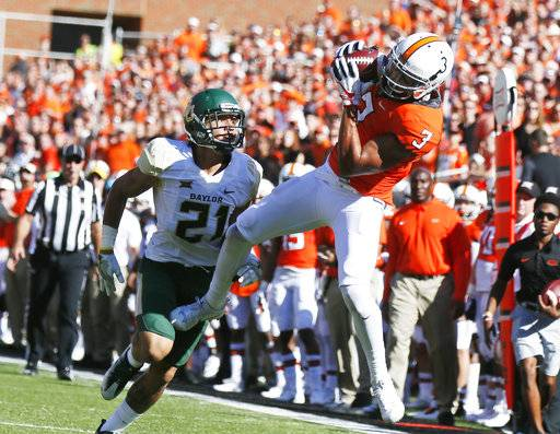 Oklahoma State wide receiver Marcell Ateman (3) catches a pass in front of Baylor cornerback Blake Lynch (21) in the second an NCAA college football game in Stillwater, Okla., Saturday, Oct. 14, 2017. (AP Photo/Sue Ogrocki)