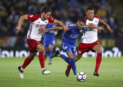 Leicester City's Riyad Mahrez, center, breaks through West Bromwich Albion's Grzegorz Krychowiak and Kieran Gibbs, right, during the English Premier League soccer match at the King Power Stadium, Leicester, England, Monday, Oct. 16, 2017. (Nick Potts/PA via AP)
