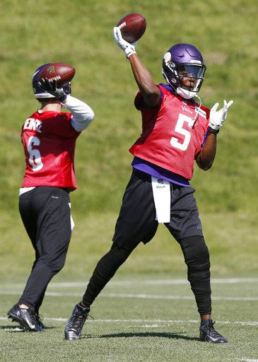 File-This June 6, 2017, file photo shows Minnesota Vikings quarterback Teddy Bridgewater, right, throwing a pass as he worked out during the NFL football teams practice in Eden Prairie, Minn. ridgewater has been cleared to rejoin the Minnesota Vikings for practice, roughly 14 months after a dislocation and multiple ligament tears in his left knee put his leg and career at risk. Coach Mike Zimmer said Bridgewater will be eased back in with the team beginning Wednesday, Oct. 18, 2017. The 24-year-old quarterback visited his surgeon Monday and was given the green light to participate on the field, effectively ending a grueling rehabilitation over the past year-plus. (AP Photo/Jim Mone, File)