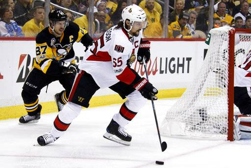 FILE - In this May 13, 2017, file photo, Ottawa Senators' Erik Karlsson (65) and Pittsburgh Penguins' Sidney Crosby (87) play during the second period of Game 1 of the Eastern Conference final in the NHL Stanley Cup hockey playoffs in Pittsburgh. Karlsson will make his season debut when the Senators host the Vancouver Canucks on Tuesday night, Oct. 17. Senators coach Guy Boucher confirmed his captain's return to the lineup at Monday's practice.(AP Photo/Gene J. Puskar, File)