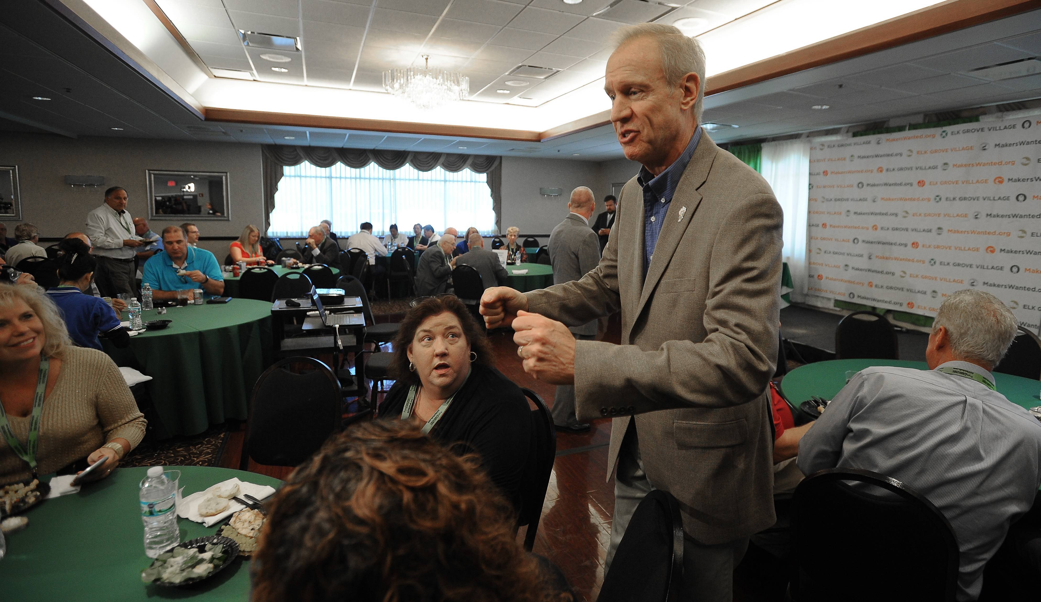 "Gov. Bruce Rauner talks to business owners during the Made in Elk Grove Manufacturing and Technology Expo on Tuesday. He reiterated his pitch to lure Amazon, saying, ""We're all in to win."""