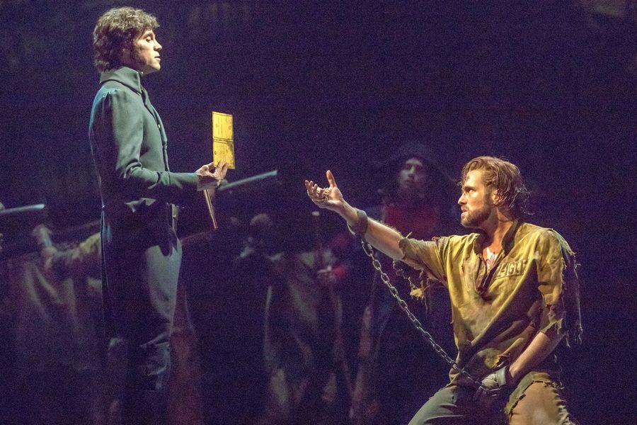 "Javert (Josh Davis), left, warns the soon-to-be-released prisoner Jean Valjean (Nick Cartell) not to violate his parole in ""Les Miserables,"" the beloved musical by Claude-Michel Schonberg and Alain Boublil. It's at the Cadillac Palace Theatre through Oct. 29."