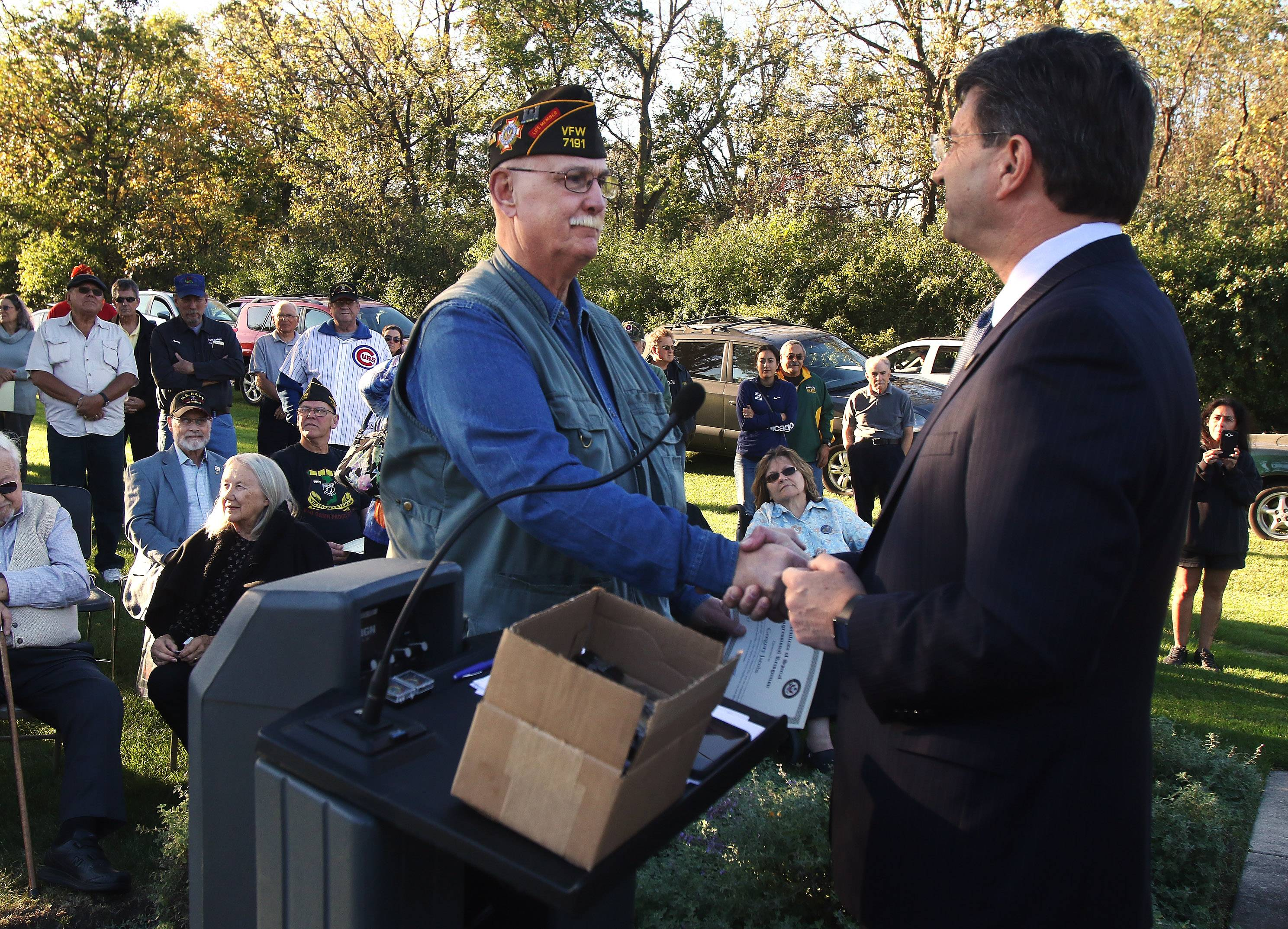 U.S. Rep. Brad Schneider hands out a Vietnam Veteran lapel pin to Gregory Jacobs of Mundelein. Jacobs was one of more than 60 veterans to attend a recognition ceremony Tuesday for veterans at the Mundelein Veterans Memorial.