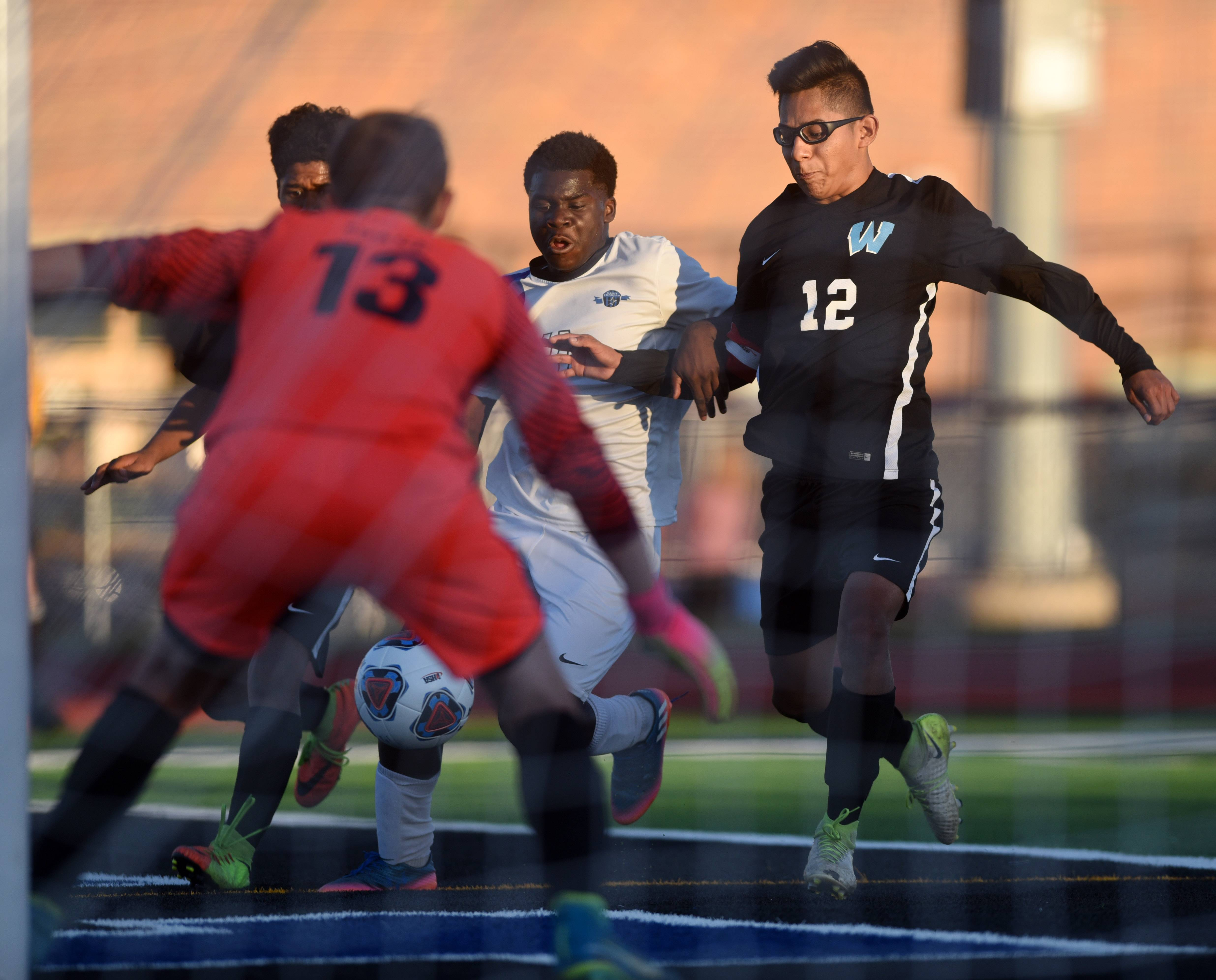 St. Charles North's Bernard Elegbede (11) fights off Willowbrook's Tomas Hernandez (12) to get off a shot with goalkeeper Mario Giase guarding the near post.