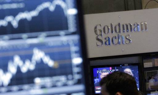 FILE - In this Oct. 16, 2014, file photo, a screen at a trading post on the floor of the New York Stock Exchange is juxtaposed with the Goldman Sachs booth. Goldman Sachs Group, Inc. reports financial results Tuesday, Oct. 17, 2017. (AP Photo/Richard Drew, File)