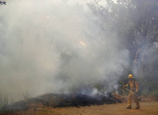 A firefighter is covered in smoke as he monitors a wildfire along a fire road Tuesday, Oct. 17, 2017, near Boulder Creek , Calif. (AP Photo/Marcio Jose Sanchez)