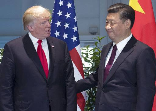 FILE - In this Saturday, July 8, 2017, file photo, U.S. President Donald Trump, left, and Chinese President Xi Jinping arrive for a meeting on the sidelines of the G-20 Summit in Hamburg, Germany. The Trump administration on Tuesday, Oct. 17, 2017, once again declined to label China a currency manipulator, even though Trump repeatedly pledged during last year's presidential campaign that he would do so as soon as he took office. (Saul Loeb/Pool Photo via AP, File)