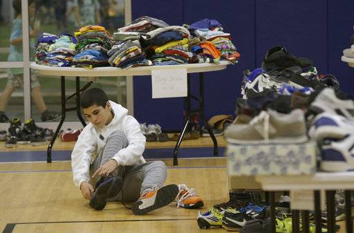 Mehdi Latrache tries on shoes at a donation center for victims of the recent wildfires, Tuesday, Oct. 17, 2017, in Santa Rosa, Calif. Latrache and his family lost their Coffey Park home a week ago as a massive wildfire swept through the area. (AP Photo/Rich Pedroncelli)