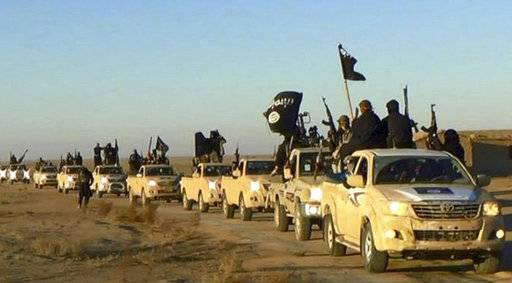FILE - In this undated file photo released by a militant website, which has been verified and is consistent with other AP reporting, militants of the Islamic State group hold up their weapons and wave its flags on their vehicles in a convoy to Iraq, in Raqqa, Syria. IS, the ultra-extremist group responsible for some of the worst atrocities perpetrated against civilians in recent history, is on the verge of collapse. The group that brutalized residents living under its command for more than three years is fighting to hang on to remaining pockets of territory in Iraq and Syria, besieged by local forces from all sides. (Militant website via AP, file)