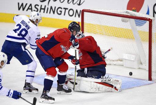 Toronto Maple Leafs right wing Connor Brown (28) watches the puck get past Washington Capitals goalie Braden Holtby, right, for his goal during the third period of a NHL hockey game, Tuesday, Oct. 17, 2017, in Washington. Also seen is Capitals center Evgeny Kuznetsov, center, of Russia. The Maple Leafs won 2-0. (AP Photo/Nick Wass)
