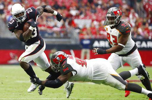 Arizona Cardinals running back Adrian Peterson (23) runs with the ball as Tampa Bay Buccaneers defensive tackle Chris Baker, center, attempts to make a tackle while Buccaneers defensive tackle Gerald McCoy (93) moves in during the second half of an NFL football game Sunday, Oct. 15, 2017, in Glendale, Ariz. (AP Photo/Ralph Freso)