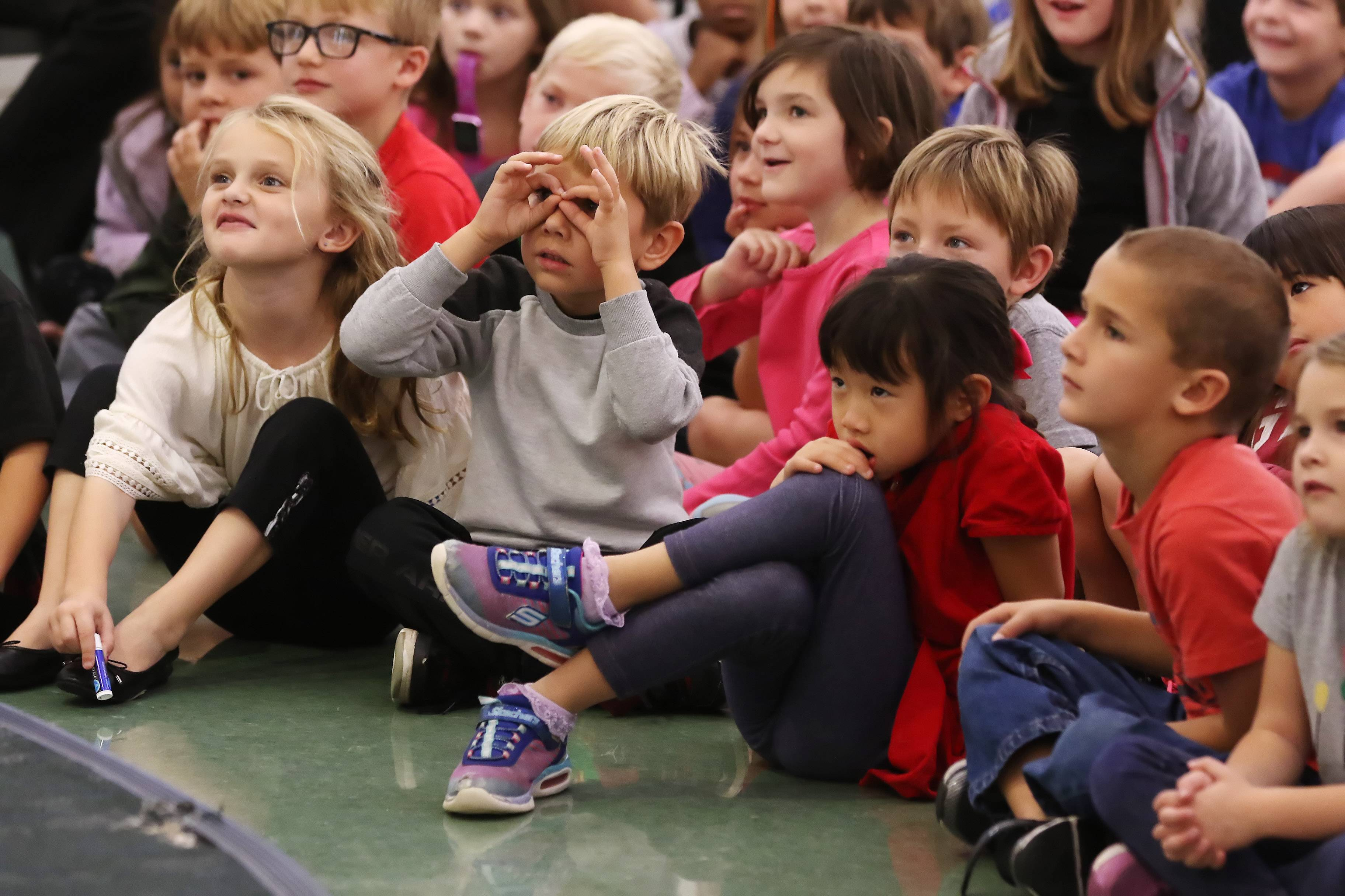 "Kindergartners Chase Weinkauf, fingers around eyes, and Elena Zhang, in red, sit with classmates watching storyteller Chris Fascione as he entertained students with his program ""Bringing Literature to Life"" on Wednesday at Copeland Manor School in Libertyville."