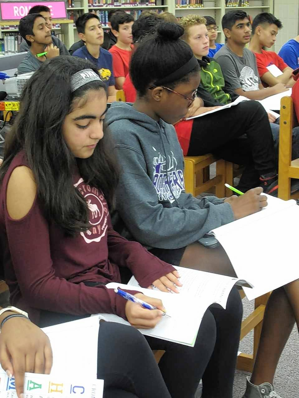 Crone Middle School eighth-graders Amisha Gambhir and Kany Ouedraogo take notes on nuclear power during a presentation to their Energy and the Environment class by two Exelon nuclear engineers, one of them a Crone graduate himself.