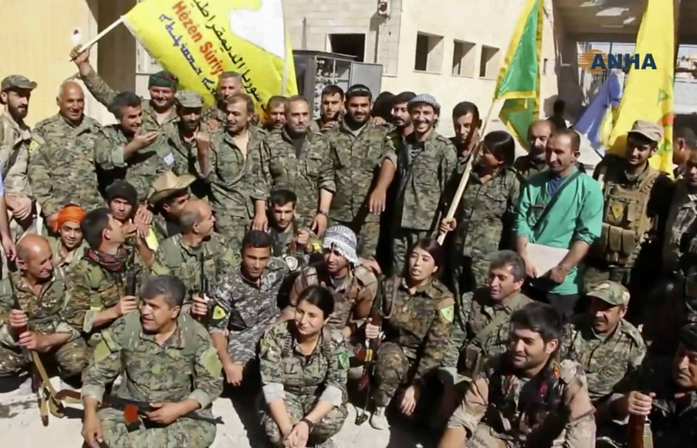 This frame grab from video released Tuesday and provided by Hawar News Agency, a Syrian Kurdish activist-run media group, shows fighters from the U.S.-backed Syrian Democratic Forces (SDF) celebrating their victory in Raqqa, Syria. U.S.-backed Syrian forces liberated the city of Raqqa from Islamic State militants on Tuesday, a senior commander for the force said, adding that clearing operations were under way to remove land mines left behind and search for the extremist group's sleeper cells.