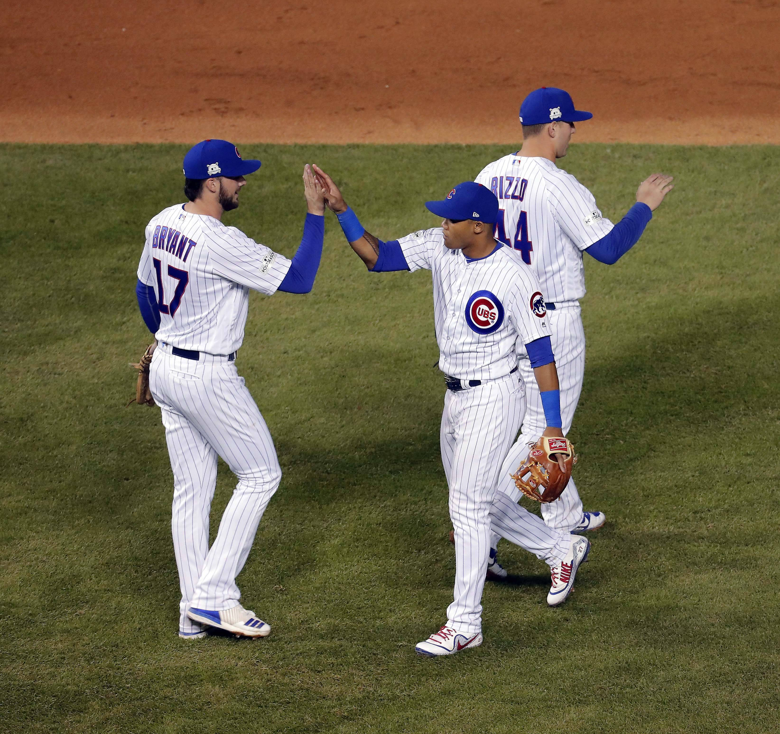 Chicago Cubs third baseman Kris Bryant (17), shortstop Addison Russell (27) and first baseman Anthony Rizzo (44) celebrate their win of Game 4 of the National League championship series, Oct, 18 2017, at Wrigley Field in Chicago.