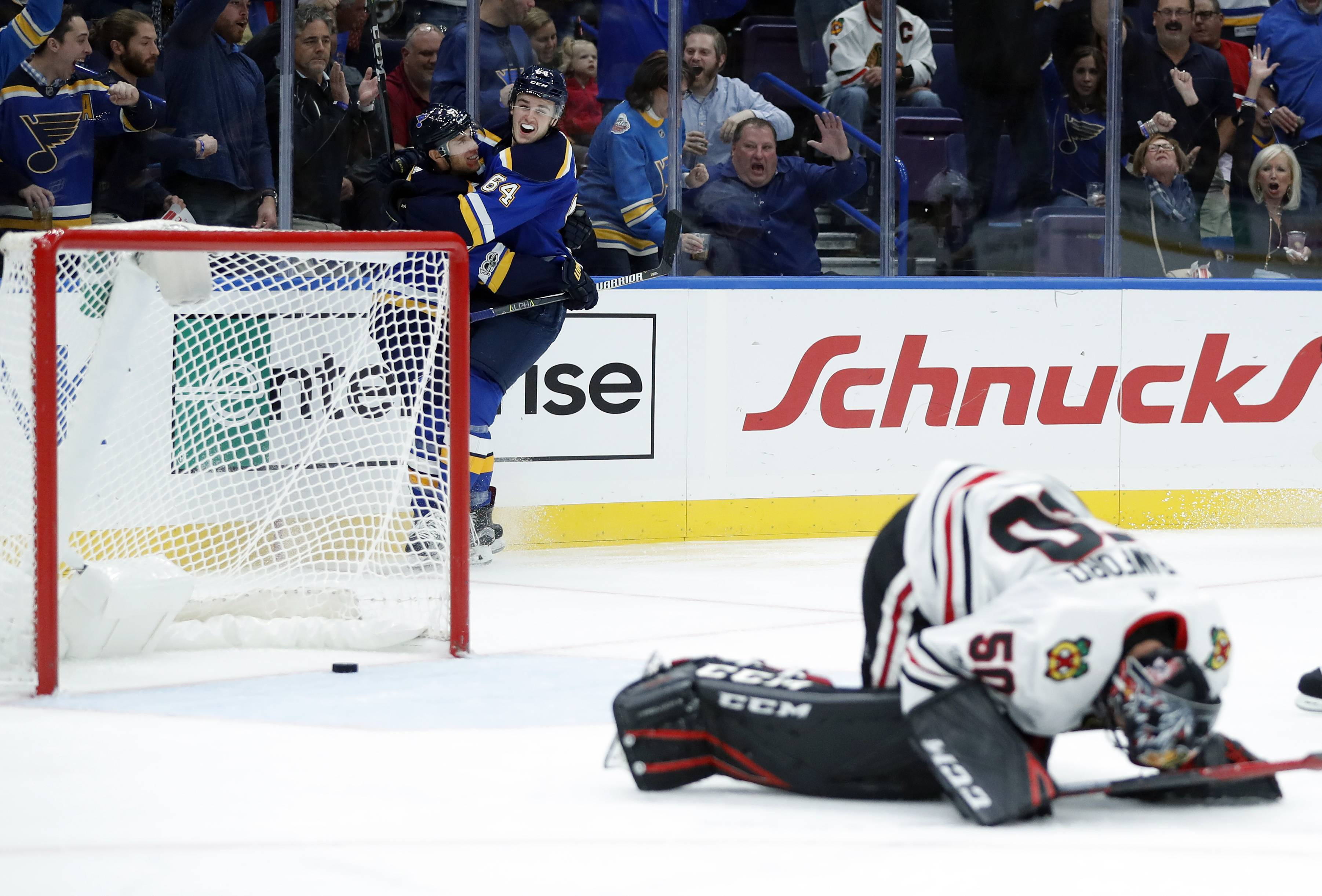 Chicago Blackhawks goalie Corey Crawford, right, reacts as St. Louis Blues' Jaden Schwartz, left, is congratulated by Sammy Blais after scoring during the second period of an NHL hockey game Wednesday, Oct. 18, 2017, in St. Louis. (AP Photo/Jeff Roberson)