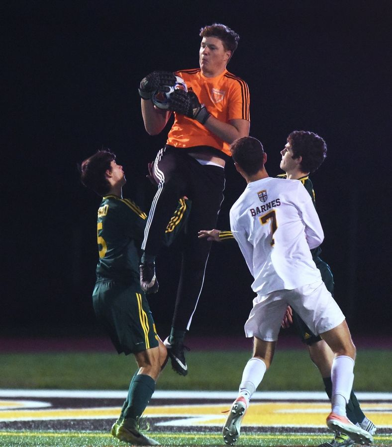 Fremd goalkeeper Jack Taraszka makes a leaping save over Carmel's Henry Barnes (7) during Class 3A regional semifinal action Wednesday in Mundelein.