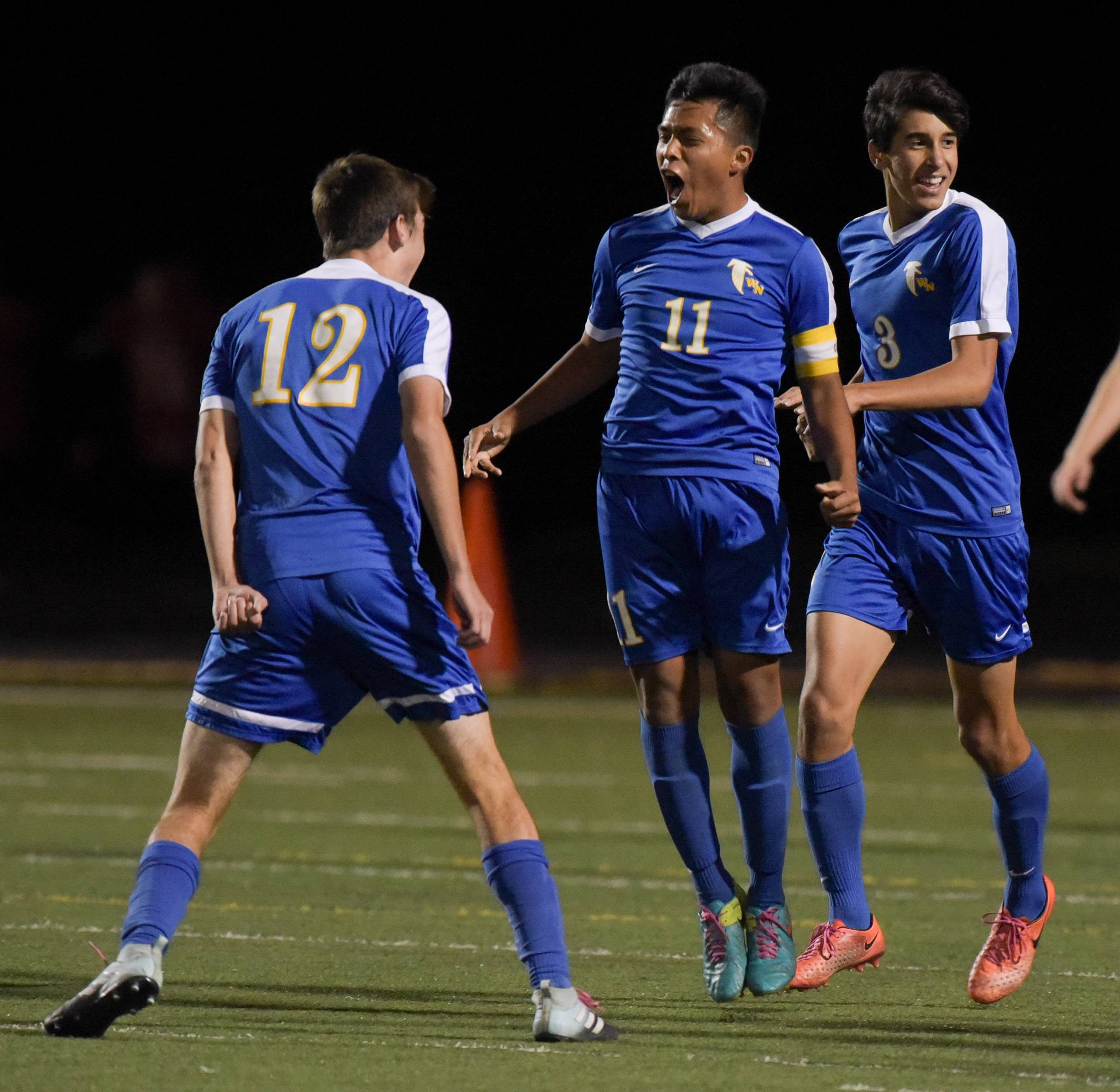 Wheaton North's Jorge Patino (11) is congratulated after his first-half goal against Conant during the Schaumburg Class 3A boys soccer regional semifinal play Wednesday.