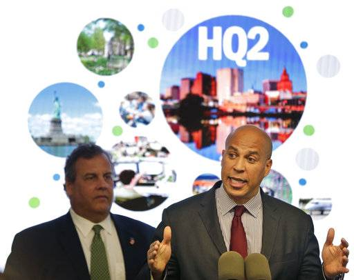 FILE - In this Monday, Oct. 16, 2017, file photo, New Jersey Sen. Cory Booker, right, speaks while New Jersey Gov. Chris Christie stands behind him during an announcement in Newark, N.J. The New Jersey lawmakers announced they are submitting a bid to Amazon that Newark would be the best location for the company's planned second headquarters. (AP Photo/Seth Wenig, File)