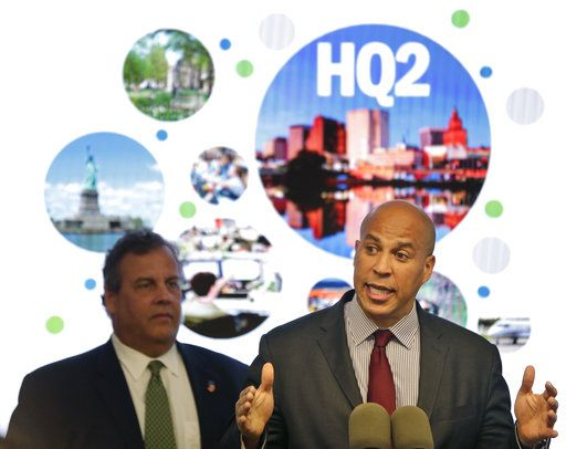 FILE - In this Monday, Oct. 16, 2017, file photo, New Jersey Sen. Cory Booker, right, speaks while New Jersey Gov. Chris Christie stands behind him during an announcement in Newark, N.J. The New Jersey lawmakers announced they are submitting a bid to Amazon that Newark would be the best location for the company's planned second headquarters.