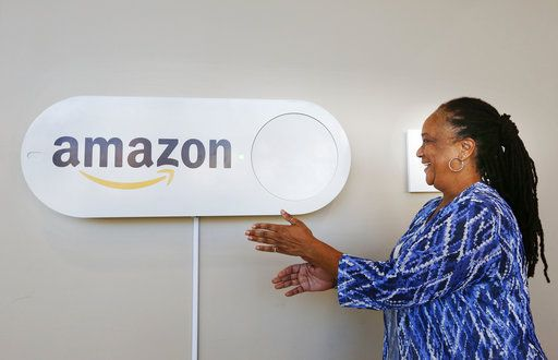 In this Monday, Oct. 16, 2017, photo, Migdawlaw Yisrael, a staffer at the University of Alabama at Birmingham's Hill Student Center, pushes a large Amazon Dash button, in Birmingham, Ala. The large Dash buttons are part of the city's campaign to lure Amazon's second headquarters to Birmingham.