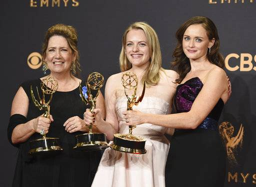 "FILE - In this Sept. 17, 2017 file photo, Ann Dowd, from left, winner of outstanding supporting actress in a drama series, Elisabeth Moss, winner of outstanding lead actress in a drama series, and Alexis Bledel, winner of outstanding guest actress in a drama for ""The Handmaid's Tale"" pose in the press room at the 69th Primetime Emmy Awards at the Microsoft Theater in Los Angeles. The Nielsen company, which has long measured viewership of television programs, announced Wednesday, Oct. 18, says it has a way to collect and widely spread details about how many people watch programming produced by streaming services. (Photo by Jordan Strauss/Invision/AP, File)"