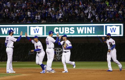Chicago Cubs' Kris Bryant (17), Jon Jay (30), Anthony Rizzo (44), Ian Happ (8) and Jason Heyward (22) celebrate after Game 4 of baseball's National League Championship Series against the Los Angeles Dodgers, Wednesday, Oct. 18, 2017, in Chicago. The Cubs won 3-2. (AP Photo/Matt Slocum)