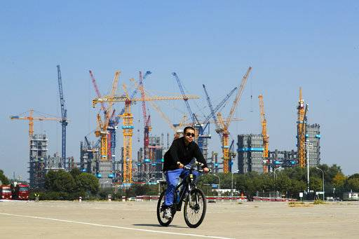 FILE - In this Oct. 5, 2017 file photo, a Chinese man rides a bicycle past a construction site near the Olympic Park in Beijing. China's ruling Communist Party is expanding its role in business even as it promises freer markets and support for entrepreneurs on the eve of President Xi Jinping's second five-year term as leader. The conflicting goals raise concerns that leaders might put off changes needed to reinvigorate a cooling economy that faces surging debt and trade tensions with Washington and Europe. (AP Photo/Andy Wong, File)
