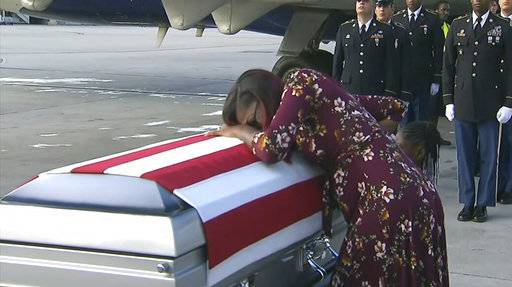 "ADDS TRUMP'S RESPONSE TO REP. WILSON - In this Tuesday, Oct. 17, 2017, frame from video, Myeshia Johnson cries over the casket of her husband, Sgt. La David Johnson, who was killed in an ambush in Niger, upon his body's arrival in Miami. President Donald Trump told the widow that her husband ""knew what he signed up for,"" according to Rep. Frederica Wilson, who said she heard part of the conversation on speakerphone. In a Wednesday morning tweet, Trump said Wilson's description of the call was ""fabricated."" (WPLG via AP)"