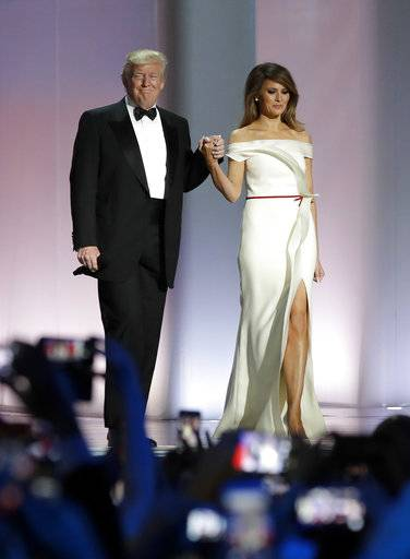 FILE - In this Jan. 20, 2017, file photo President Donald Trump arrives with first lady Melania Trump at the Liberty Ball in Washington. Melania Trump is donating her inaugural ball gown to the first ladies' collection at the Smithsonian Institution. The first lady is handing over the vanilla silk, off-the-shoulder gown during a ceremony on Oct. 20. (AP Photo/Patrick Semansky, File)