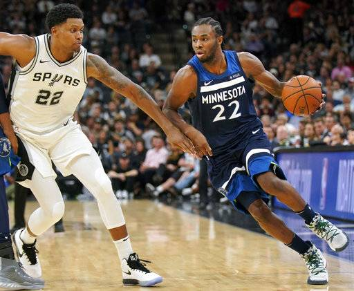 Minnesota Timberwolves' Andrew Wiggins, right, drives around San Antonio Spurs' Rudy Gay during the first half of an NBA basketball game, Wednesday, Oct. 18, 2017, in San Antonio. (AP Photo/Darren Abate)