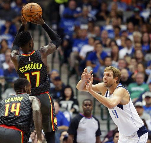 Atlanta Hawks guard Dennis Schroder (17) of Germany shoots against Dallas Mavericks forward Dirk Nowitzki (41) of Germany during the first half of an NBA basketball game in Dallas, Wednesday, Oct. 18, 2017. (AP Photo/LM Otero)