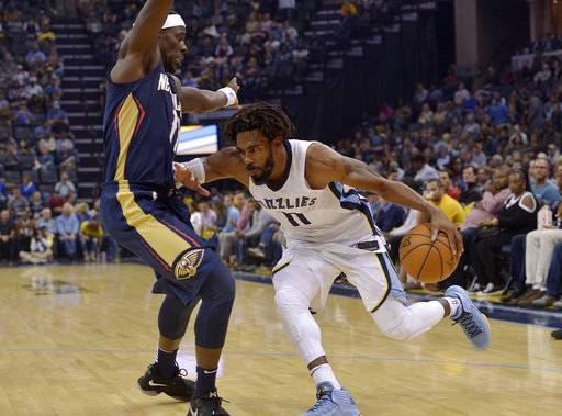 Memphis Grizzlies guard Mike Conley, right, drives against New Orleans Pelicans guard Jrue Holiday during the second half of an NBA basketball game Wednesday, Oct. 18, 2017, in Memphis, Tenn. (AP Photo/Brandon Dill)
