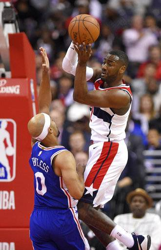 Washington Wizards guard John Wall (2) looks to pass as Philadelphia 76ers guard Jerryd Bayless (0) defends during the first half of an NBA basketball game, Wednesday, Oct. 18, 2017, in Washington. (AP Photo/Nick Wass)