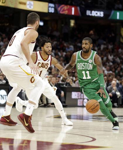 Boston Celtics' Kyrie Irving (11) drives past Cleveland Cavaliers' Kevin Love (0) and Derrick Rose (1) in the first half of an NBA basketball game, Tuesday, Oct. 17, 2017, in Cleveland. The Cavaliers won 102-99. (AP Photo/Tony Dejak)