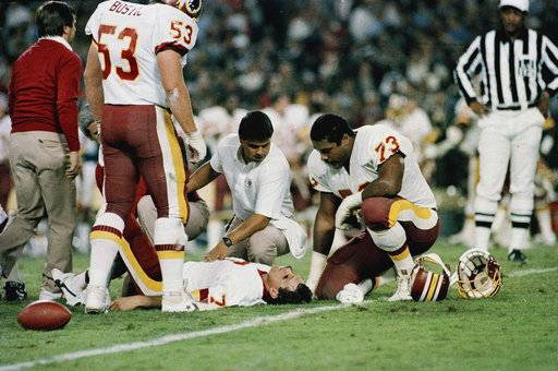FILE - In this Nov. 18, 1985, file photo, Washington Redskins quarterback Joe Theismann lies on the ground after he injured his right leg during the first half of an NFL game against the New York Giants at RFK Stadium in Washington. Former NFL quarterback Joe Theismann saw the video of Boston Celtics forward Gordon Hayward's broken left ankle and immediately felt a kind of empathy few could. (AP Photo/J. Scott Applewhite, File)