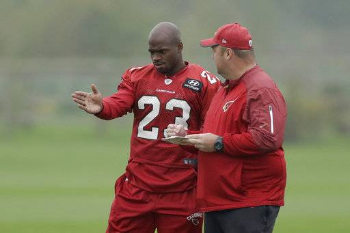 Arizona Cardinals running back Adrian Peterson, left, speaks with Running Backs coach Freddie Kitchens during an NFL training session at the London Irish rugby team training ground in the Sunbury-onThames suburb of south west London, Wednesday, Oct. 18, 2017. The Arizona Cardinals are preparing for an NFL regular season game against the Los Angeles Rams at London's Wembley stadium on Sunday. (AP Photo/Matt Dunham)