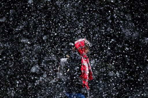 A woman walks through a winter snow storm in Philadelphia in March 2017. In a report released Thursday, Oct. 19, U.S. forecasters say chances are good that much of the nation will have a warmer than normal winter.
